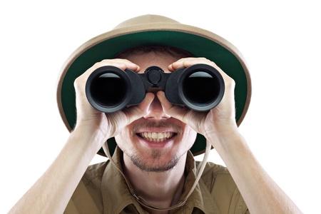 Heureux jeune homme portant une chemise safari et casque colonial en regardant à travers des jumelles, isolé sur blanc, close-up Banque d'images