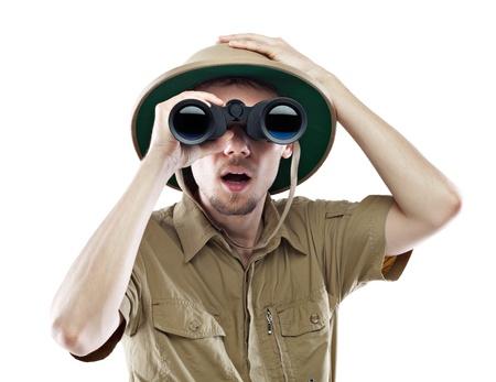 médula: Hombre joven mirando a través de binoculares con una expresión sorprendida, aislado en blanco