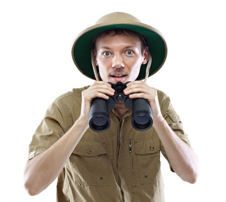 pith: Young man wearing safari shirt and pith helmet lowering binoculars, isolated on white background Stock Photo