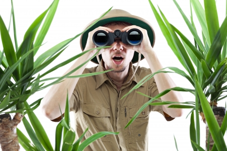 Young man looking through binoculars with an amazed expression, palm trees on foreground out of focus, isolated on white Standard-Bild