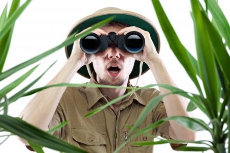 médula: Hombre joven mirando a través de binoculares con una expresión sorprendida, palmeras en primer plano fuera de foco, aislado en blanco