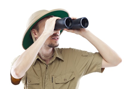 Young man wearing pith helmet looking through binoculars, isolated on white