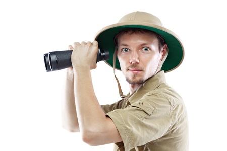 médula: Hombre joven que desgasta la camisa de safari y binoculares médula casco que sostiene, aislados en fondo blanco, vista lateral