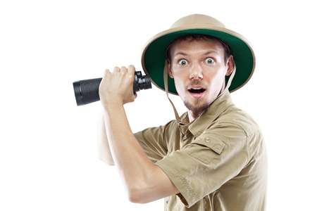 Surprised young man wearing a pith helmet and holding binoculars, isolated on white Stockfoto