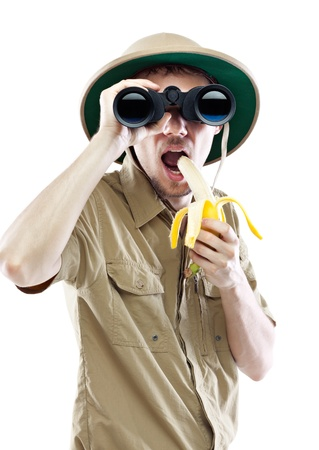 Young man wearing a pith helmet looking through a pair of binoculars and eating banana, isolated on white  photo