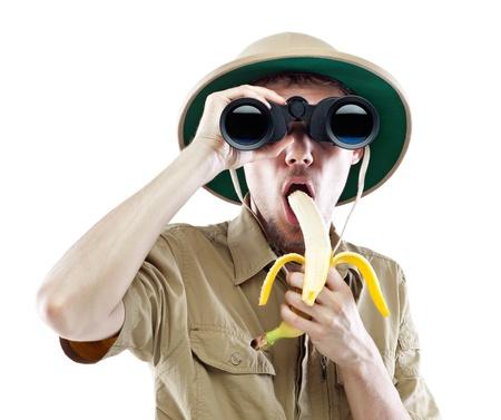 m�dula: Hombre joven que llevaba un casco de m�dula mirando a trav�s de un par de binoculares y comer pl�tanos, aislado en blanco