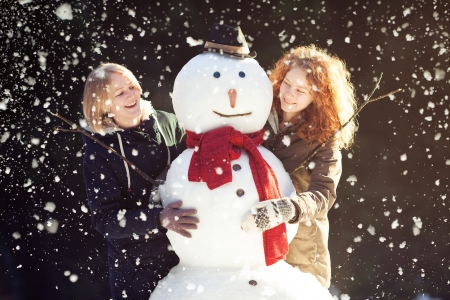 Two smiling pretty girls posing with a snowman in forest, it's snowing, dark background, focus on snowman photo