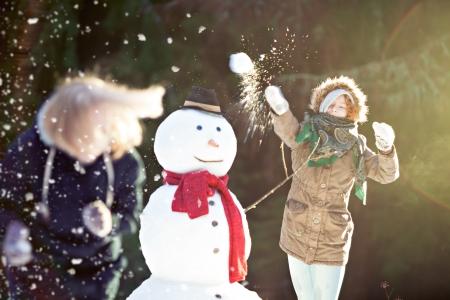 boule de neige: Snowball fight. Jeune femme jetant de boules de neige au point, le flou de mouvement Banque d'images