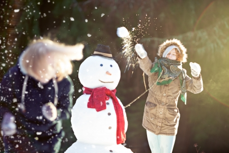 snowball: Snowball fight. Young woman throwing snowball in focus, motion blur Stock Photo
