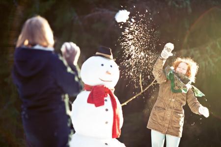boule de neige: Deux filles ayant bataille de neige. L'un d'eux jeter boule de neige est la mise au point, le flou de mouvement