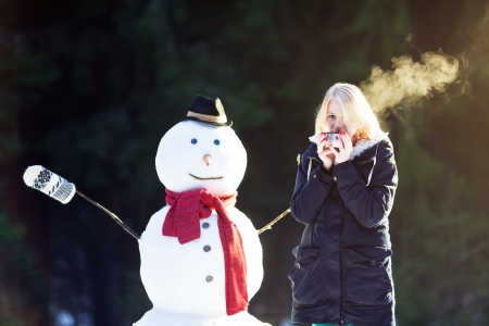 Pretty blond girl drinking hot tea outside with snowman