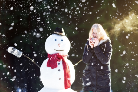Pretty blond girl dinking tea outdoors with snowman while its snowing photo