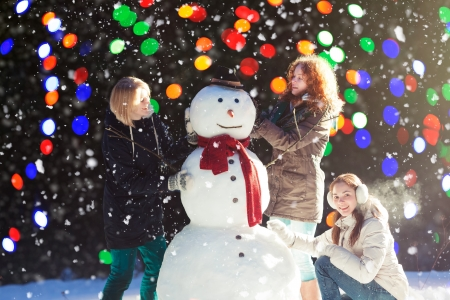 Beautiful young women enjoying building a snowman on a snowy winter day, blurred lights on background photo
