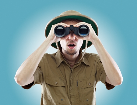 Young man wearing a pith helmet looking through a pair of binoculars with a surprised expression, on blue background