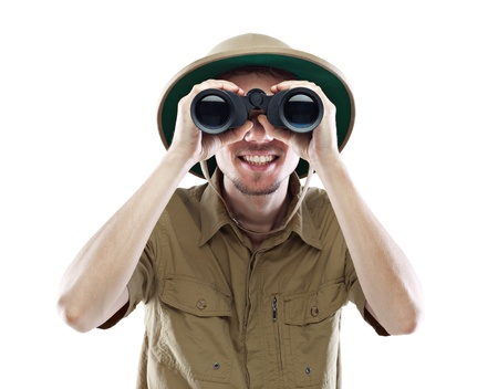 Young smiling man wearing pith helmet looking through binoculars, isolated on white