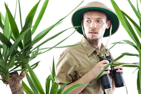 m�dula: Hombre joven usando binoculares m�dula casco sosteniendo y mirando algo �rboles incre�bles, palmeras en primer plano fuera de foco, aislado en blanco