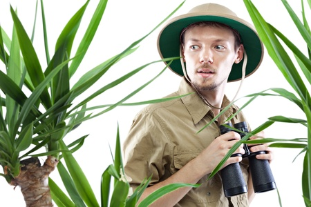 Young man wearing pith helmet holding binoculars and staring at something amazing, palm trees on foreground out of focus, isolated on white Stock Photo - 17394776
