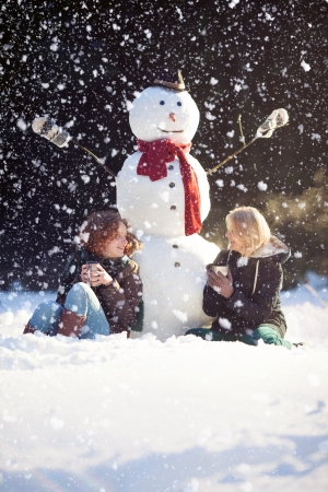 Two young woman sitting near snowman and drinking hot tea while it photo