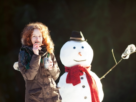 Pretty red-haired girl dinking tea and eating gingerbread outdoors with snowman, sunny winter day photo