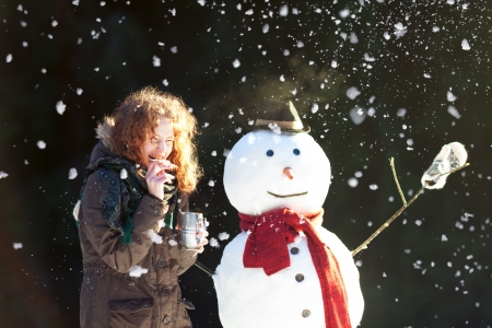 Pretty red-haired girl dinking tea and eating gingerbread outdoors with snowman while its snowing photo