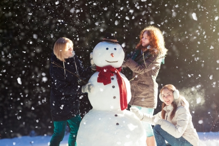 Beautiful young women enjoying building a snowman on a snowy winter day in forest Фото со стока