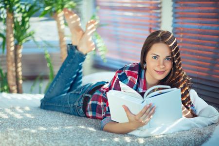 Jonge mooie vrouw liggend op haar buik en lezen