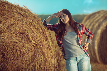 Portrait of young woman next to a stack of hay photo