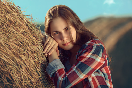 Portrait of young woman next to a stack of hay in sunlight photo