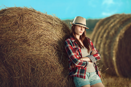 Portrait of young woman standing next to a stack of hay in sunlight photo