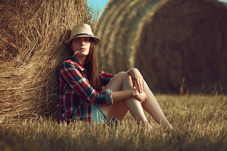 Portrait of young woman sitting next to a stack of hay in sunlight photo