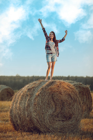 Cheerful young woman standing on a stack of hay in sunlight photo