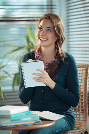 Young woman writing a wishlist 免版税图像 - 35266985