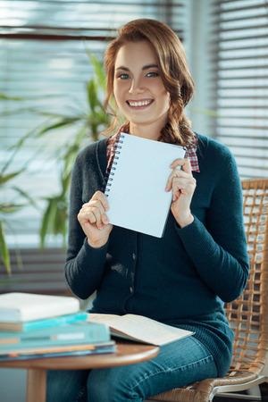 Pretty student showing a blank notebook Фото со стока