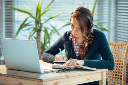 Young woman wearing headphones and making notes