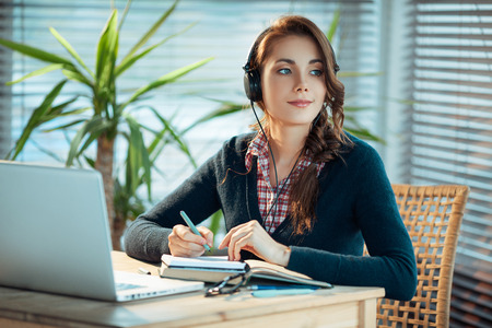 Young woman wearing headphones and studying