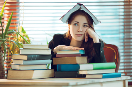 tedious: Portrait of beautiful student girl sitting among books with a book on her head Stock Photo