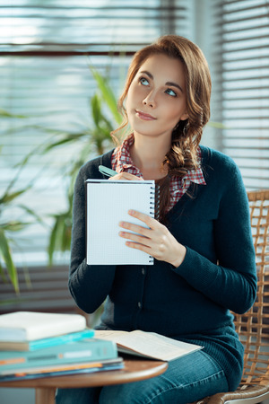 Young woman writing a to do list