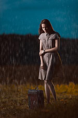 sotto la pioggia: Giovane donna con una valigia in piedi sotto la pioggia e in attesa Archivio Fotografico