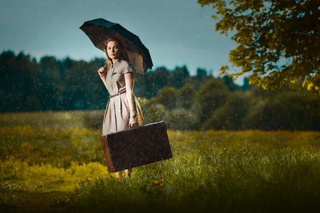 sotto la pioggia: Giovane donna a piedi con una valigia sotto la pioggia Archivio Fotografico