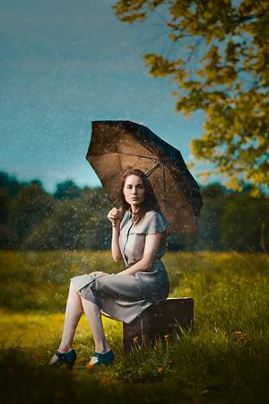 sotto la pioggia: Giovane donna seduta su una valigia sotto la pioggia e in attesa