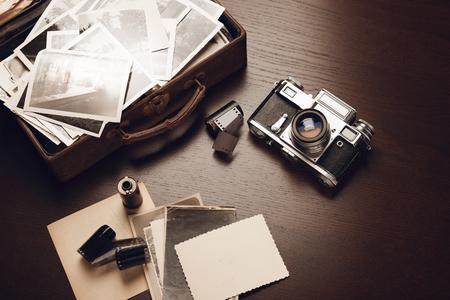 Caso con viejas fotografías en blanco y negro, cámara de la película y rollos de película; tarjeta en blanco en primer plano (todas las fotos son mías)