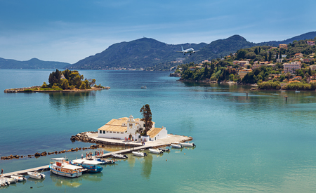 Typical view of Vlacherna Monastery and Mouse island with airplane landing, Corfu, Greece.
