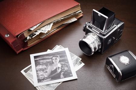 álbum de foto rojo con las viejas fotos y la cámara del formato medio en la mesa de madera