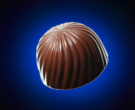 chocolate candy: Chocolate candy isolated on dark blue background Stock Photo