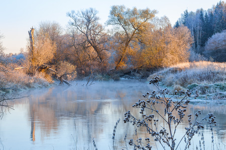 rime frost: Winter landscape with a vapouring river on frost and trees covered with hoar Stock Photo