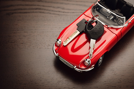locked in: Model of a red car with padlock on wooden surface, view from above. Concept of buying or selling a car. Close up, copy space. Stock Photo