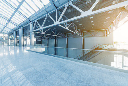 corridors: Escalators and corridors of modern office building or airport, glass walls and reflective floor, natural light and flare