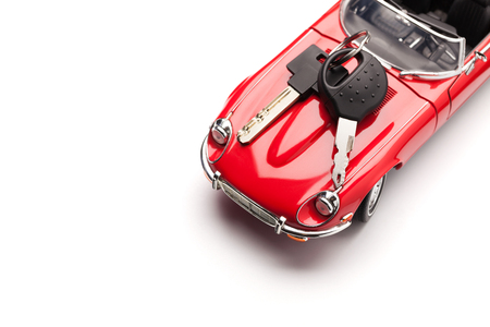 concept car: Model of a red car with padlock on white background, view from above. Concept of buying or selling a car. Close up, copy space.