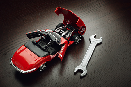 Concept of repair, maintenance and servicing of machines. Model of red cabriolet with opened doors and hood and wrench on wooden surface Archivio Fotografico