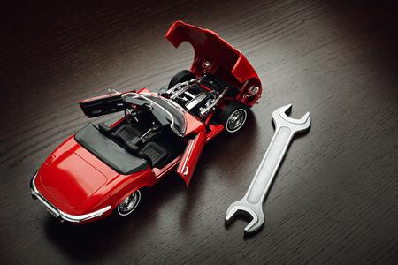 Koncepcja naprawy, konserwacji i obsługi maszyn. Model czerwony kabriolet z otwartymi drzwiami i maską i klucz na powierzchni drewnianych Zdjęcie Seryjne
